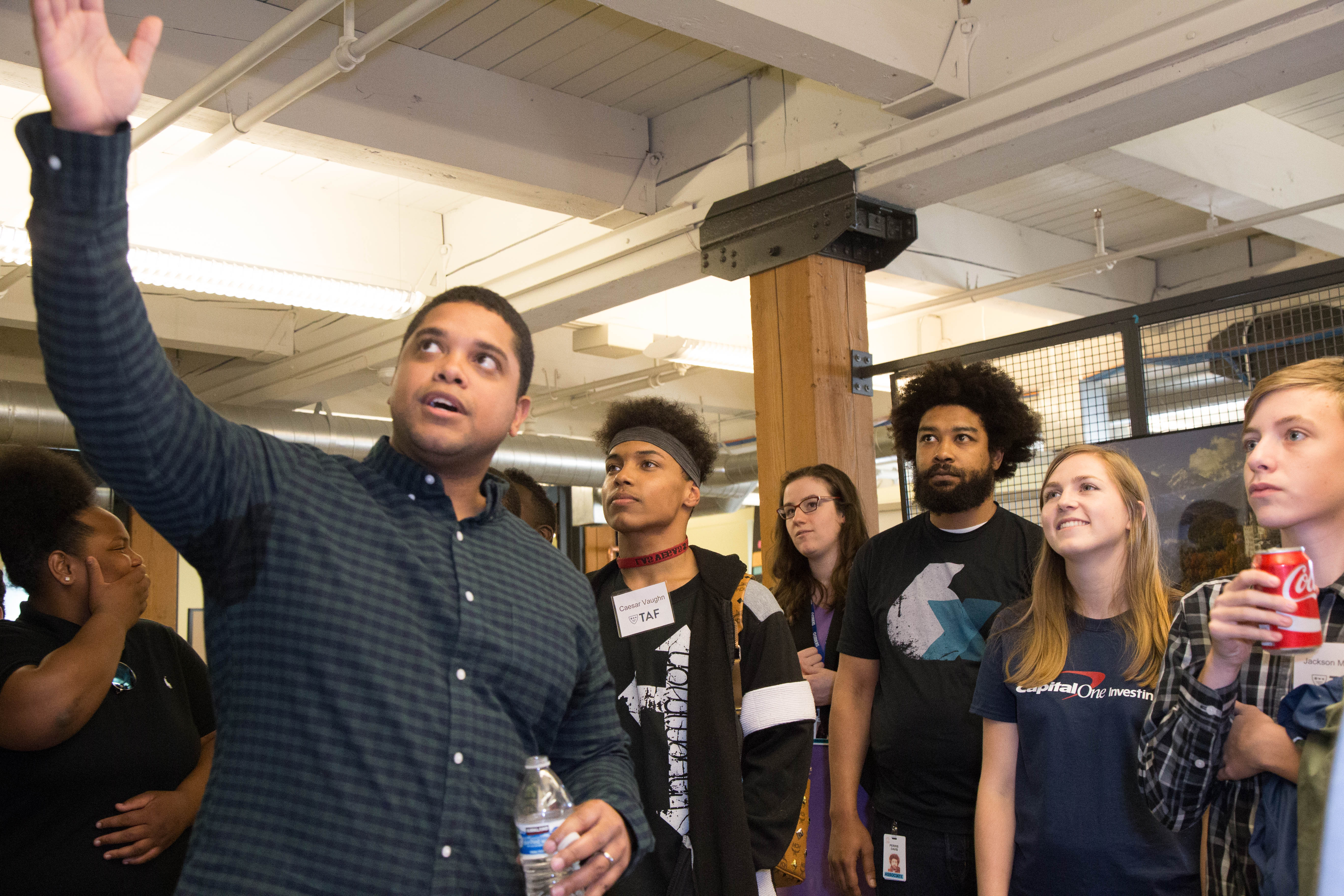 Shortly after arriving at Capital One's downtown Seattle offices, the TAF students were led on a workspace tour by local associates including Mike Bailey (foreground), Natalie Griffin (fourth from right), Perris Davis (third from right) and Alison Wyllie (second from right.)