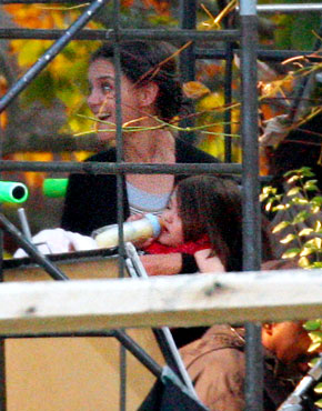 Suri Cruise drinks from a bottle in New York